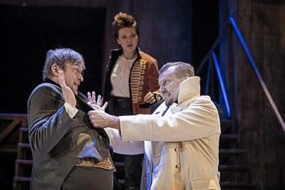 Teatteriesitys, etualalla nainen, taustalla kaksi miestä 1800-luvun alun puvuissa.