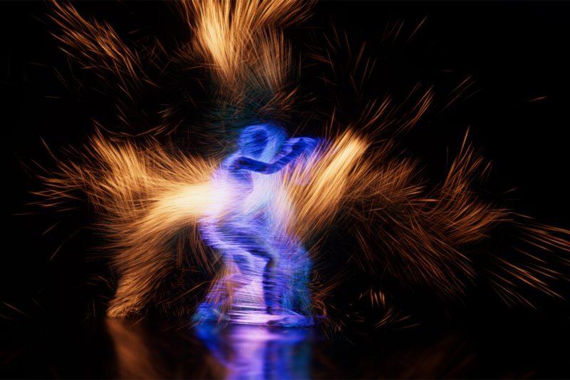 Valolähdesäteitä teatterinäyttämöllä liikkuvan ihmisen ääriviivoista.