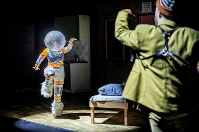 Avaruuspukuinen nainen tanssii.