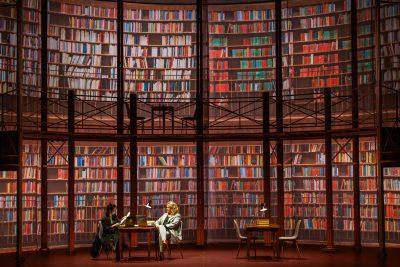 Nainen kirjastossa esityksessä Dosentit.