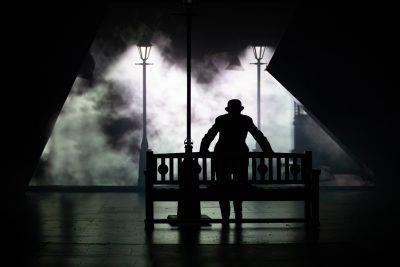 Mies seisoo pimeällä näyttämöllä.